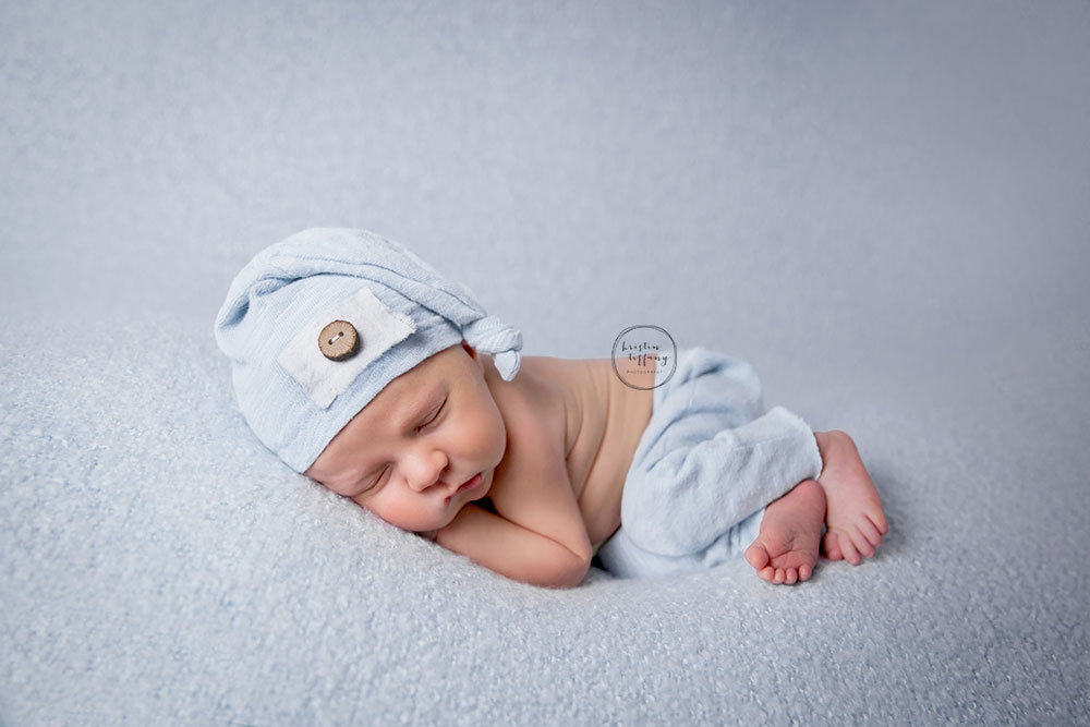 a posed newborn session of a baby boy in blue
