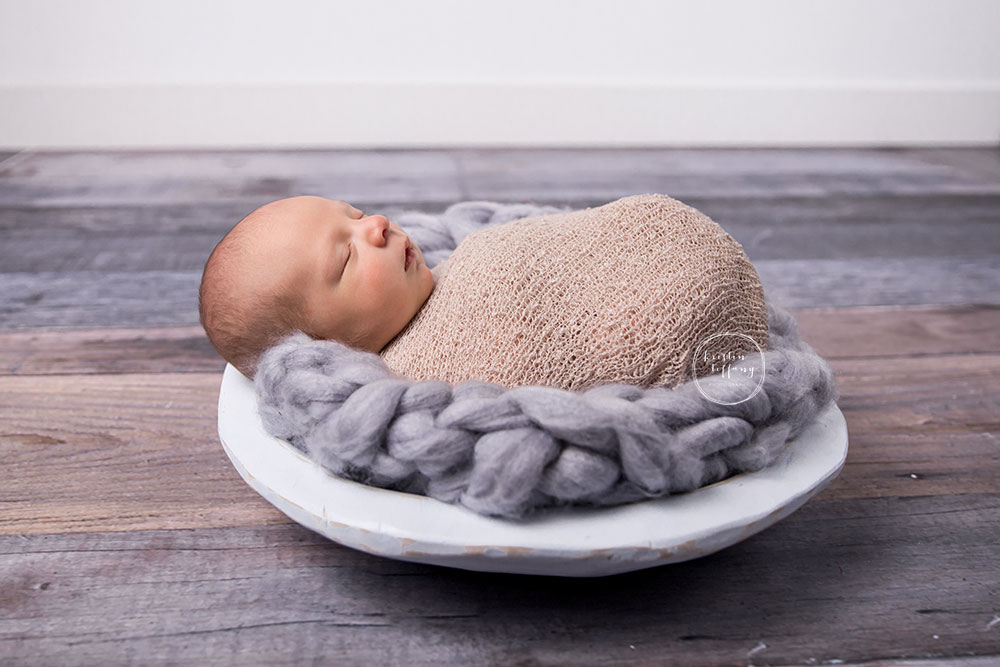 a posed newborn session of a baby boy in a wooden bowl