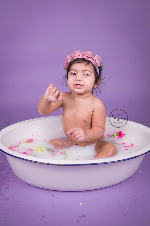 a photo of a baby girl post cake smash floral milk bath