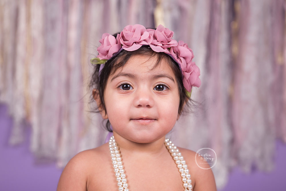 a photo of a baby girl wearing a floral halo and pearl necklace