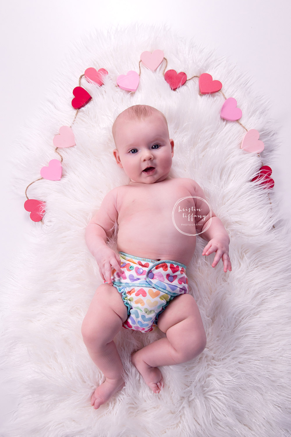 a photo of a baby girl surrounded by hearts in a heart cloth diaper