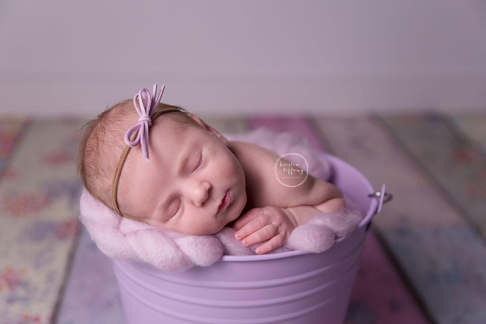 a newborn photo of a newborn baby girl sleeping in a bucket