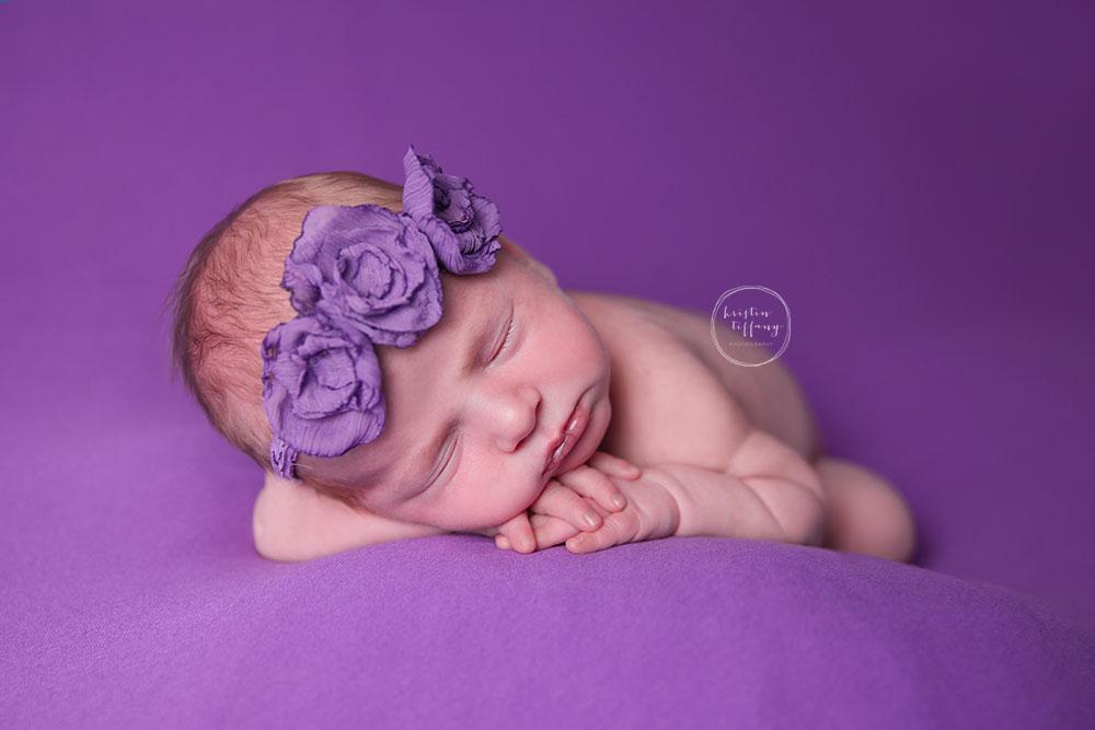 a newborn photo of a baby girl in a purple headband