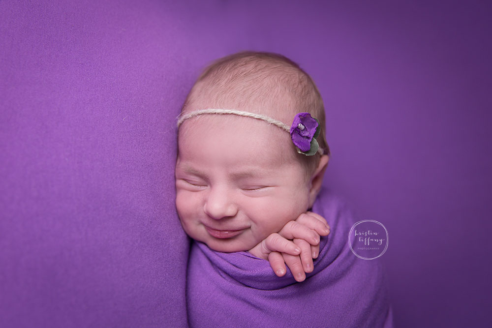 a newborn photo of a smiling baby girl