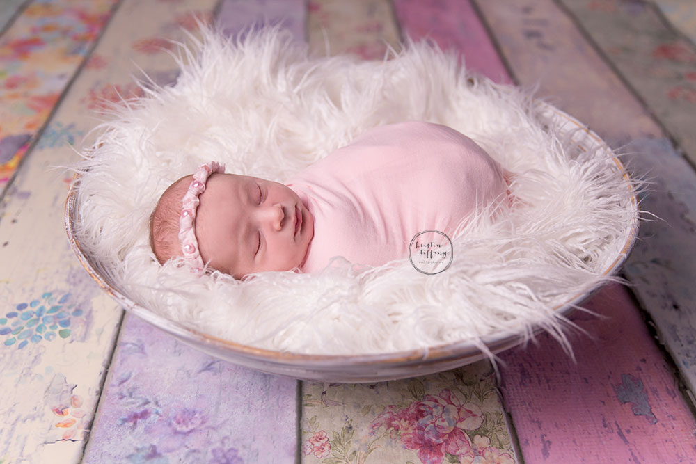 a newborn photo of a baby girl on a floral wood floordrop