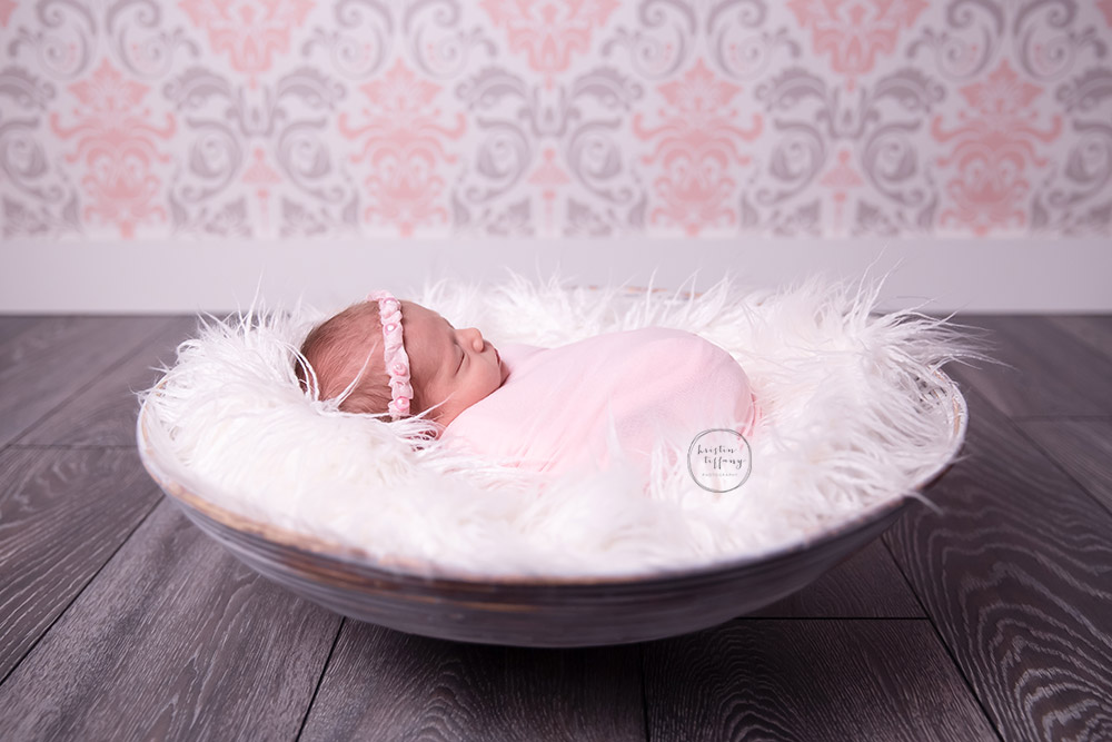 a newborn photo of a baby girl posed in a bowl
