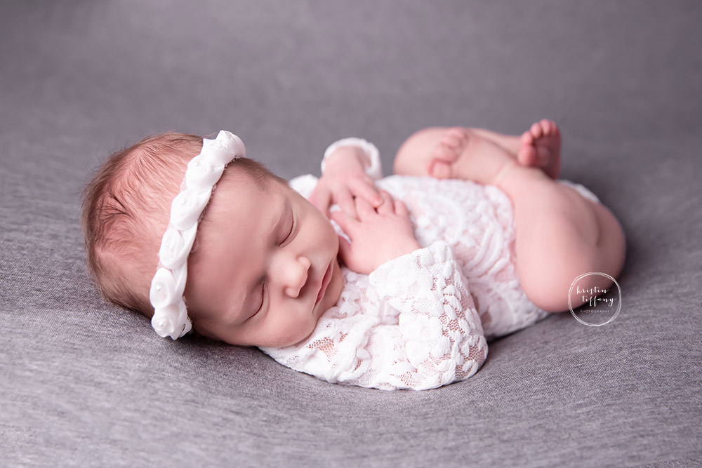 a photo of a newborn baby girl posed on grey fabric in a lace ropmer