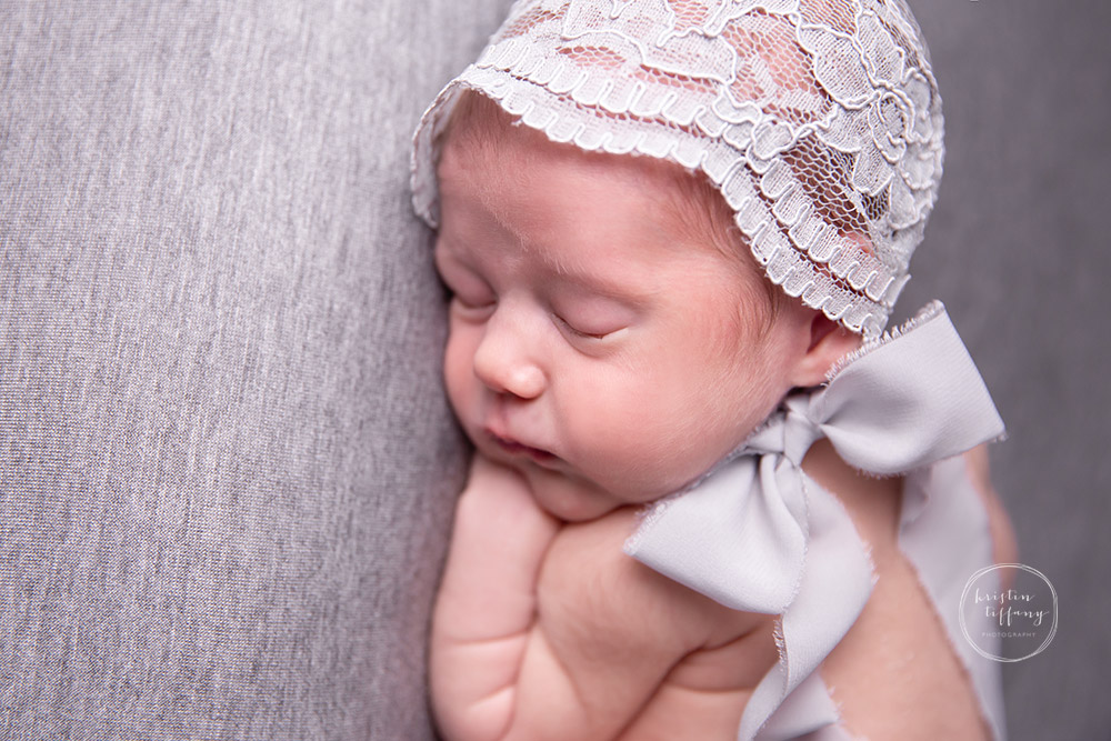 a newborn photo of a baby girl in a grey lace bonnet