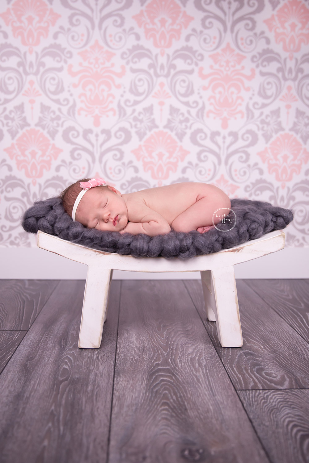 a newborn photo of a baby girl posed on a wooden stool