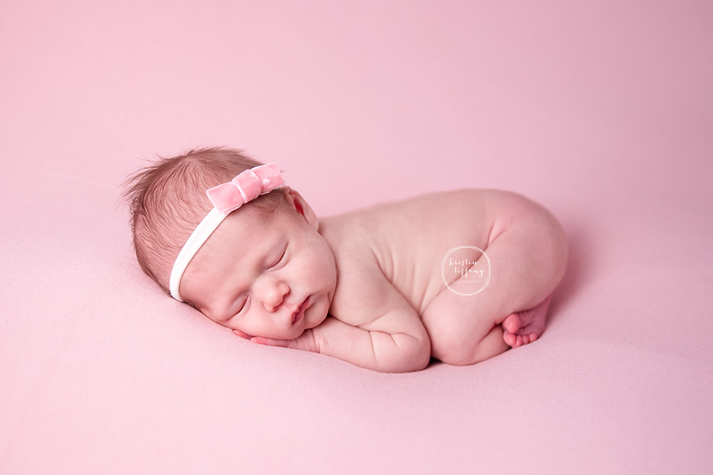 a newborn photo of a baby girl posed on pink fabric