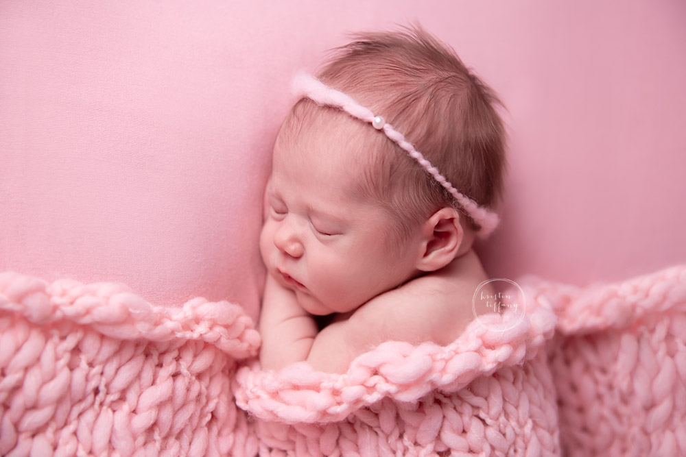 a newborn photo of a baby girl posed with a pink knit blanket
