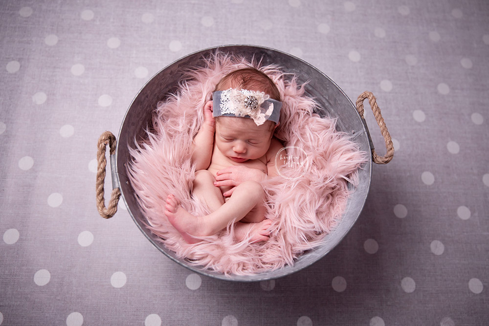 a newborn photo of a baby girl posed in a bucket
