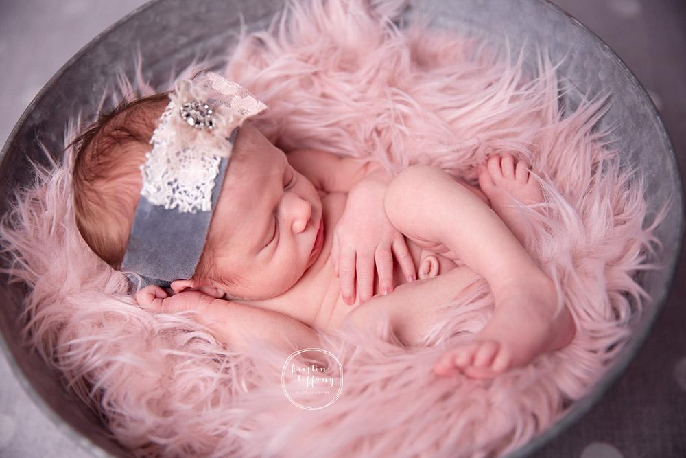 a photo of a newborn curled in a fur rug