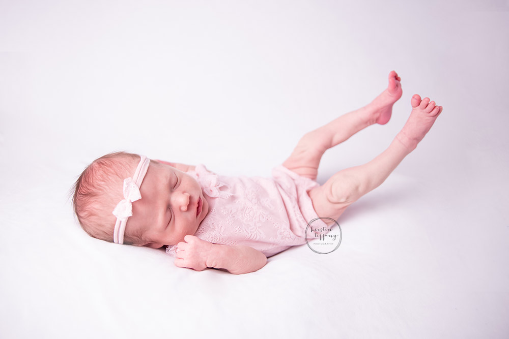a photo of a newborn baby girl stretching her legs