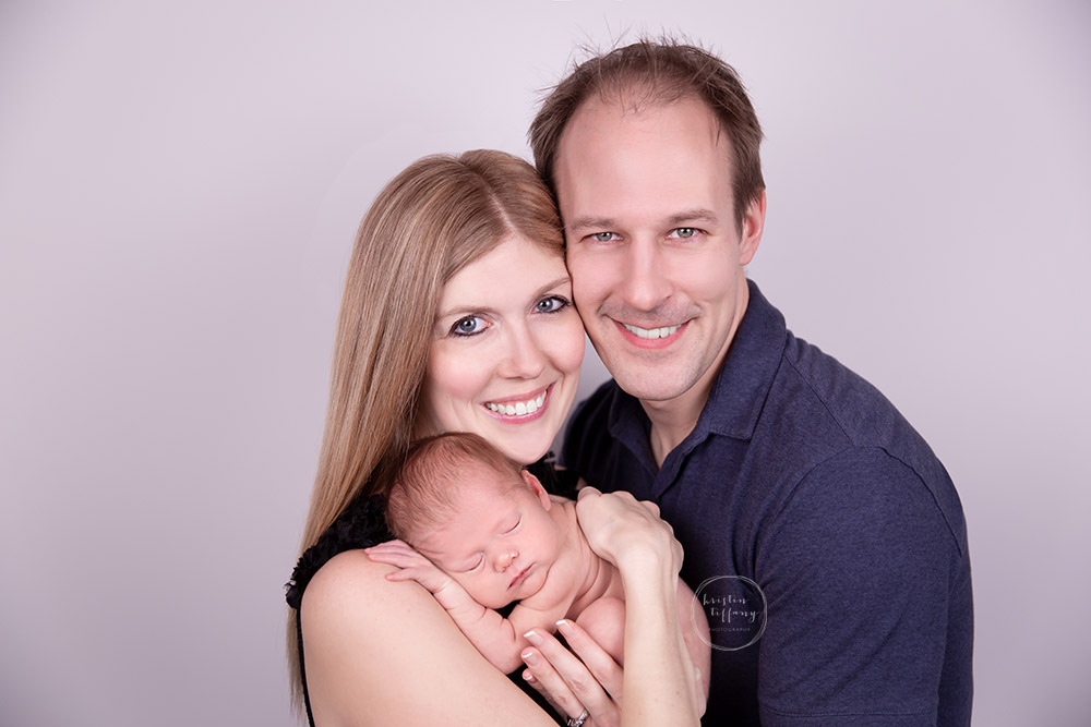 a newborn photo with baby and her parents