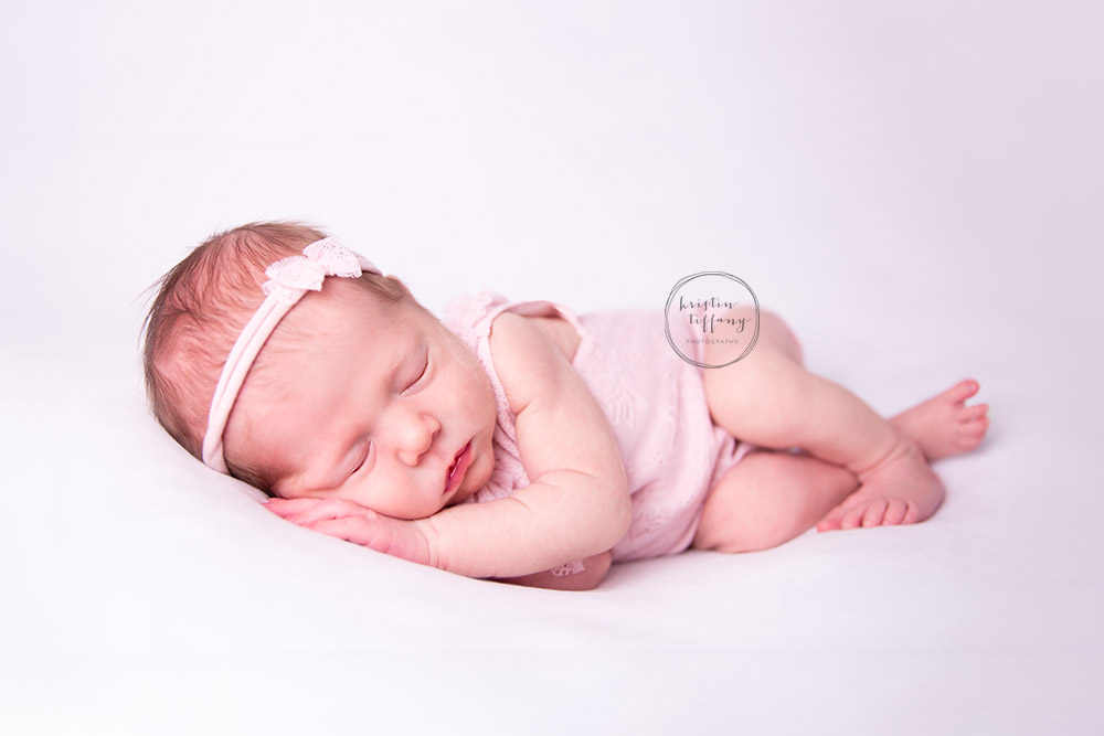 a newborn photo of a baby girl posed on a white backdrop