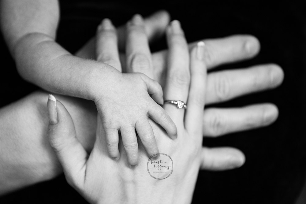 a newborn photo of baby and parents hands