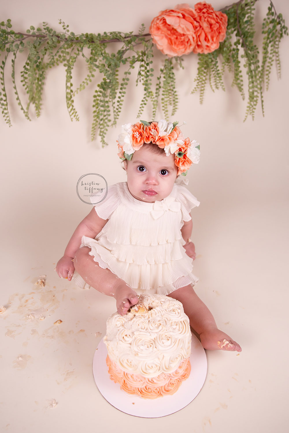 a photo of a baby girl putting her foot in her birthday cake