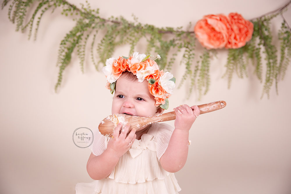 a photo of a baby girl eating cake with a big wooden spoon