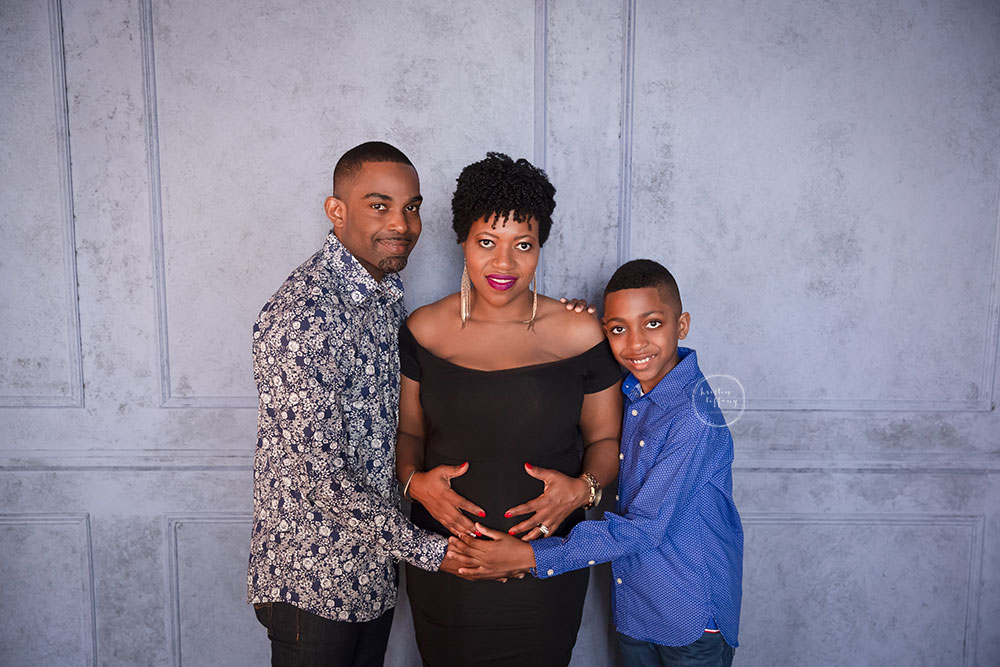 a maternity photo of a mother with her husband and son