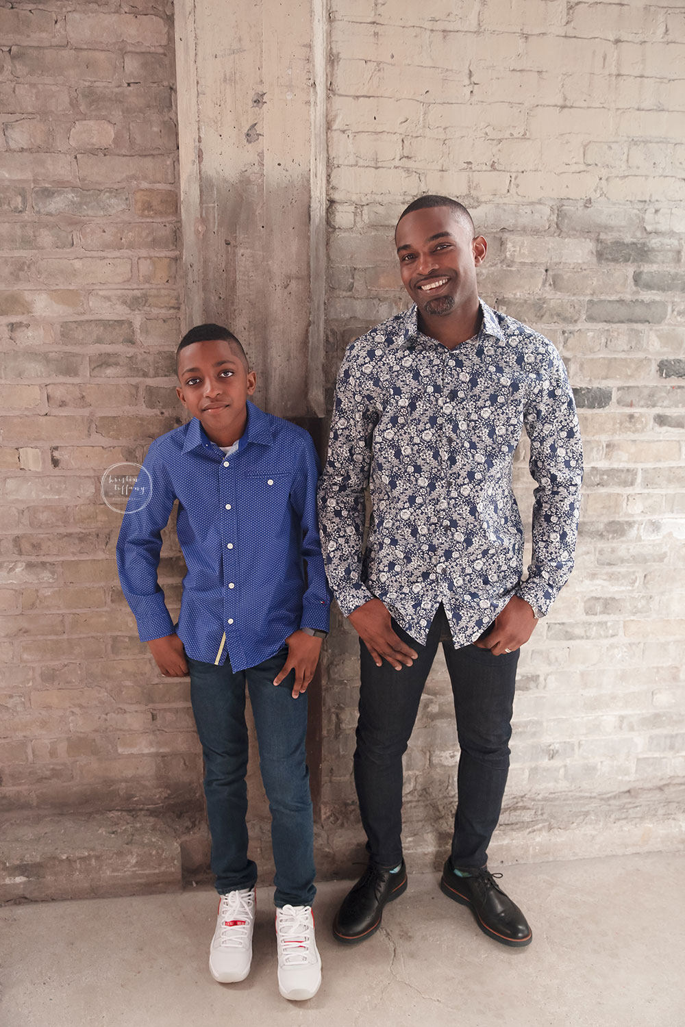 a photo of a father and son by a brick wall