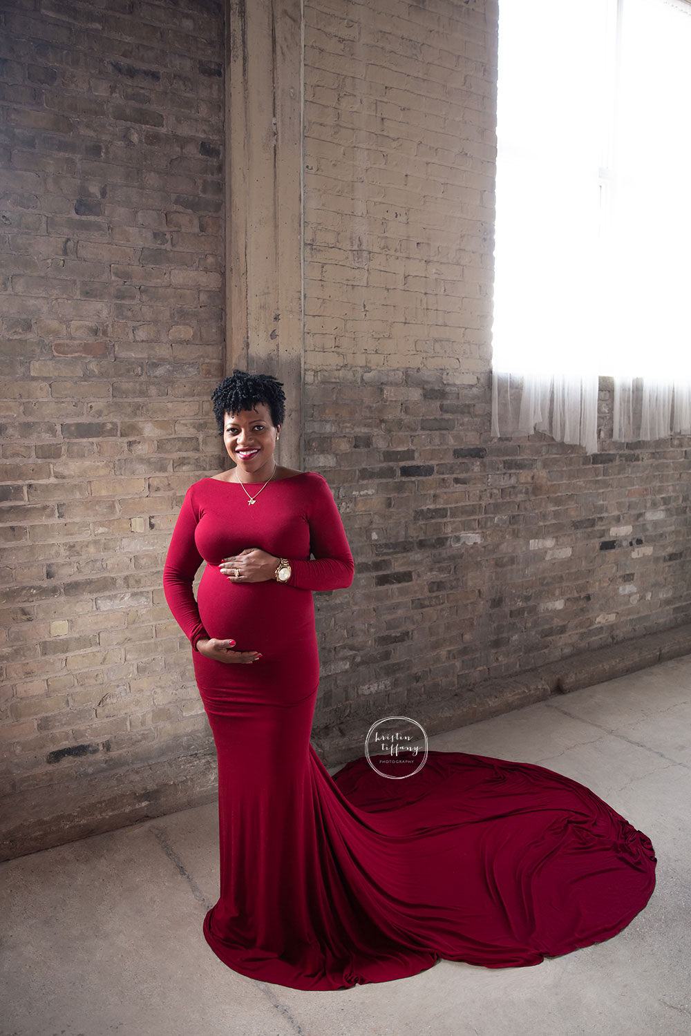a maternity photo of a woman in a red gown