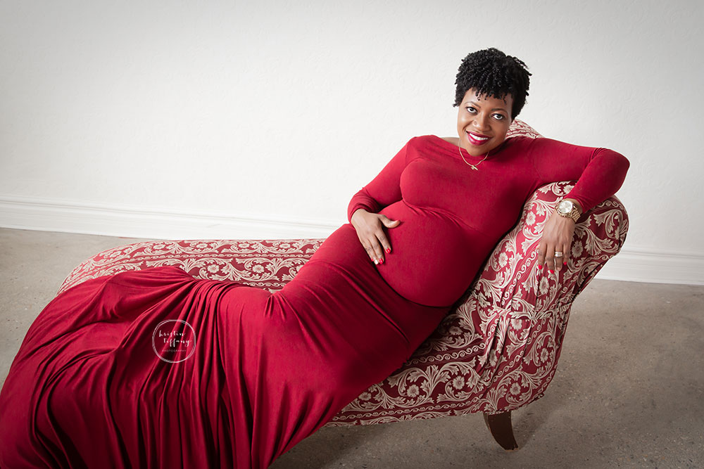 a maternity photo of a woman in a red gown on a chaise