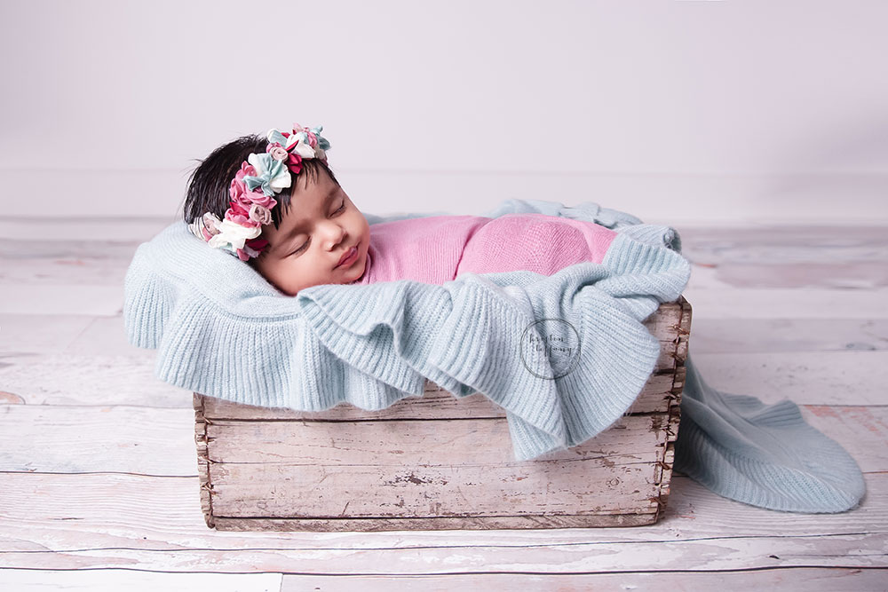 a photo of a baby girl asleep in a wooden crate