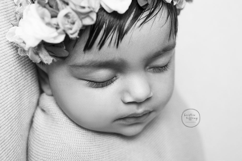 a black and white photo of a sleeping baby girl