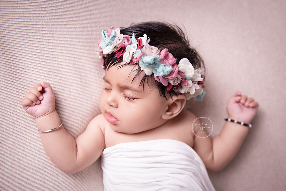 a photo of a baby girl sleeping at a baby photo session