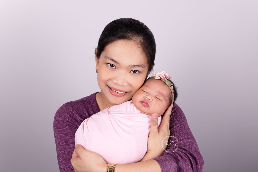 a photo of a newborn baby girl with her mother at a newborn photoshoot