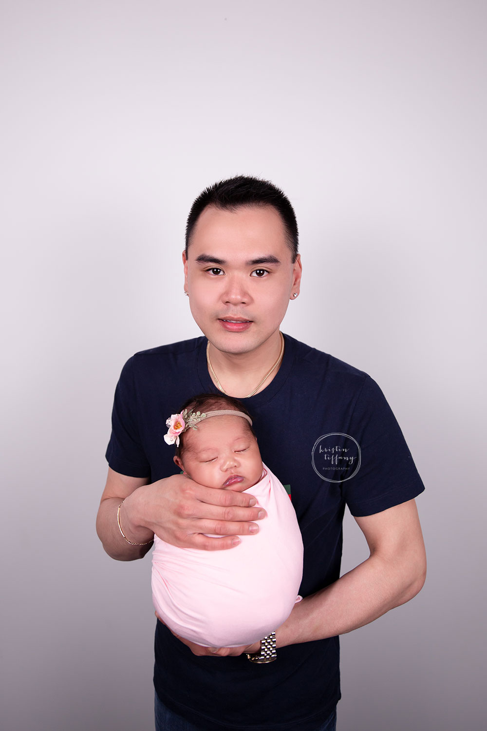 a photo of a newborn baby girl with her father at a photoshoot