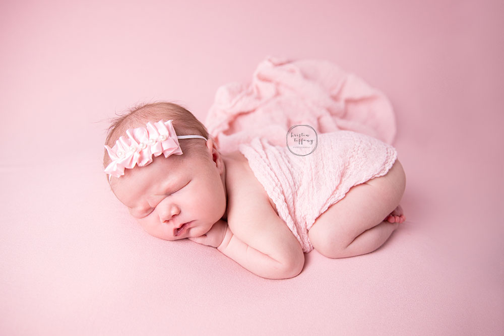 a newborn photo of a baby girl at a photoshoot