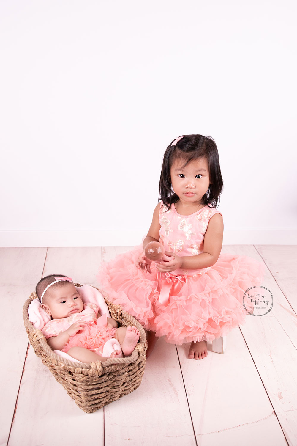 a photo of a baby girl and her sister at her photo session