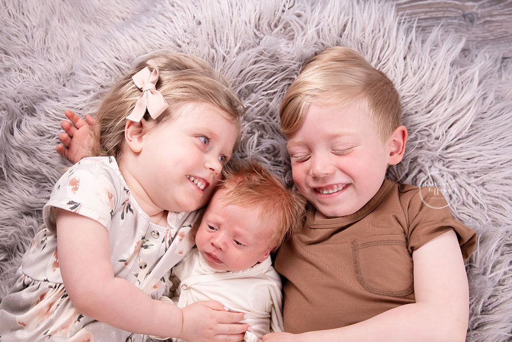 a photo of baby boy and his siblings at his newborn photo session