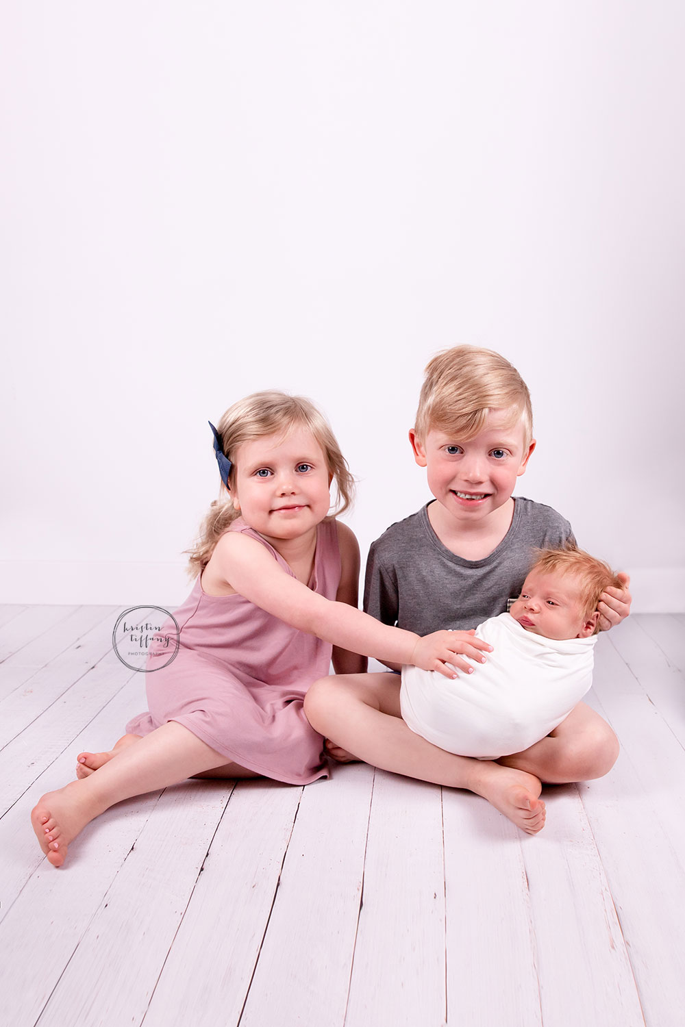a photo of baby boy at his siblings at a newborn photo session
