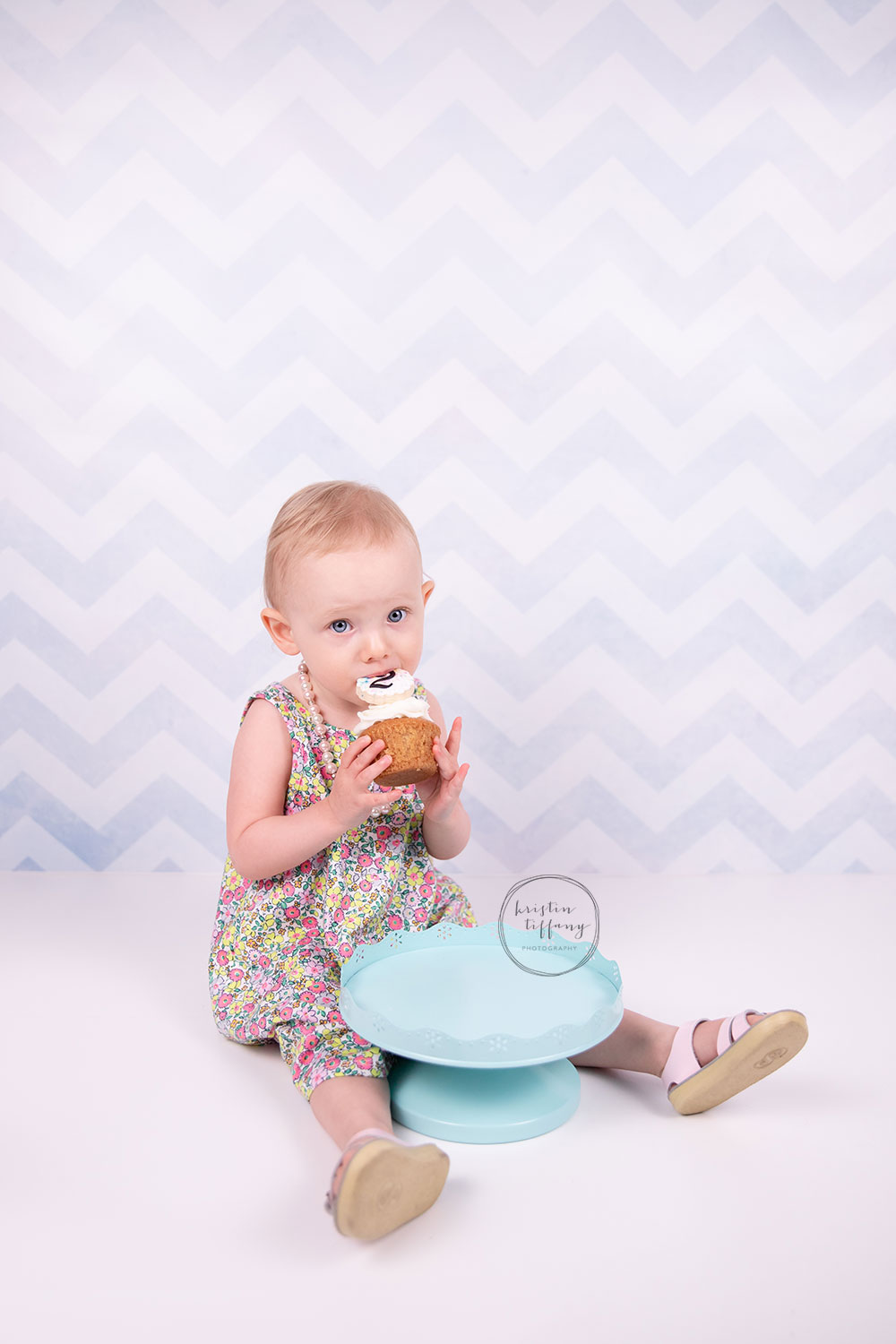 a photo of a baby girl eating a cupcake at a photoshoot