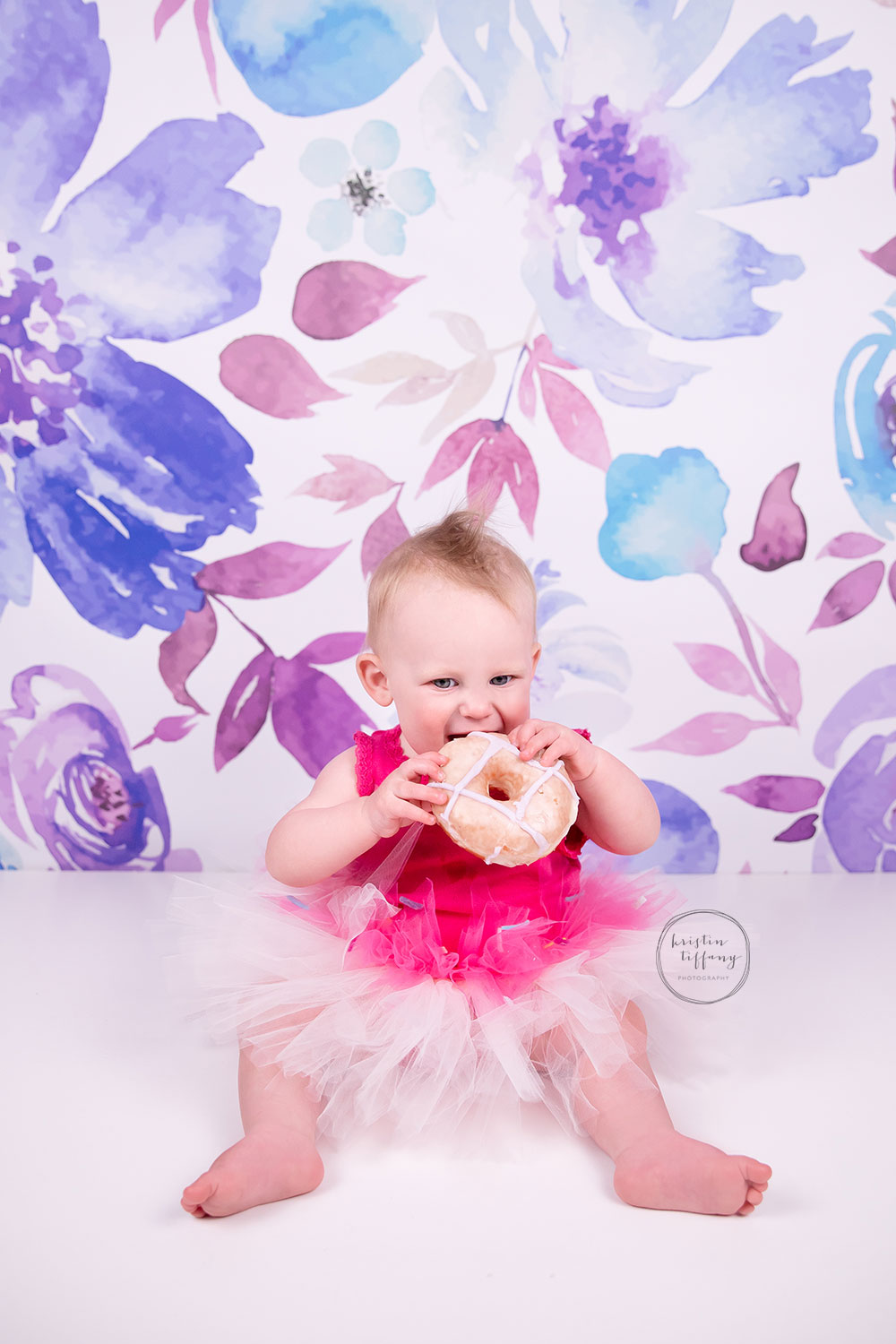 a photo of a baby eating a donut at a photoshoot
