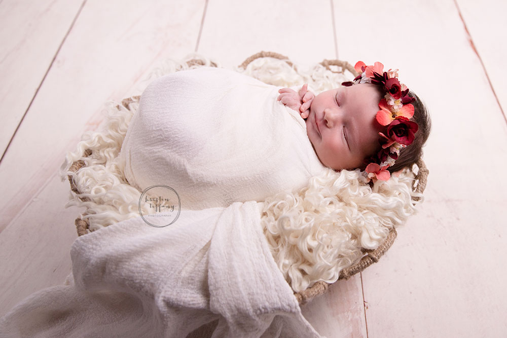 a photo of a newborn baby girl at her newborn photoshoot