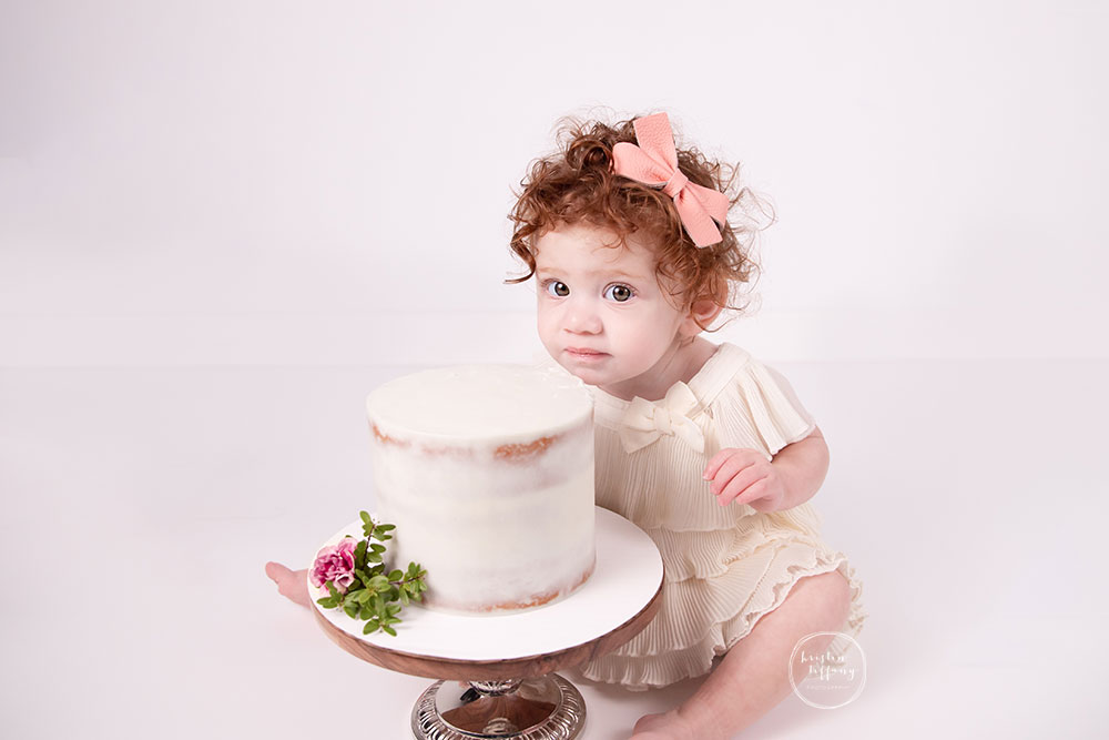 a photo of a sweet baby girl at a cake smash photo session