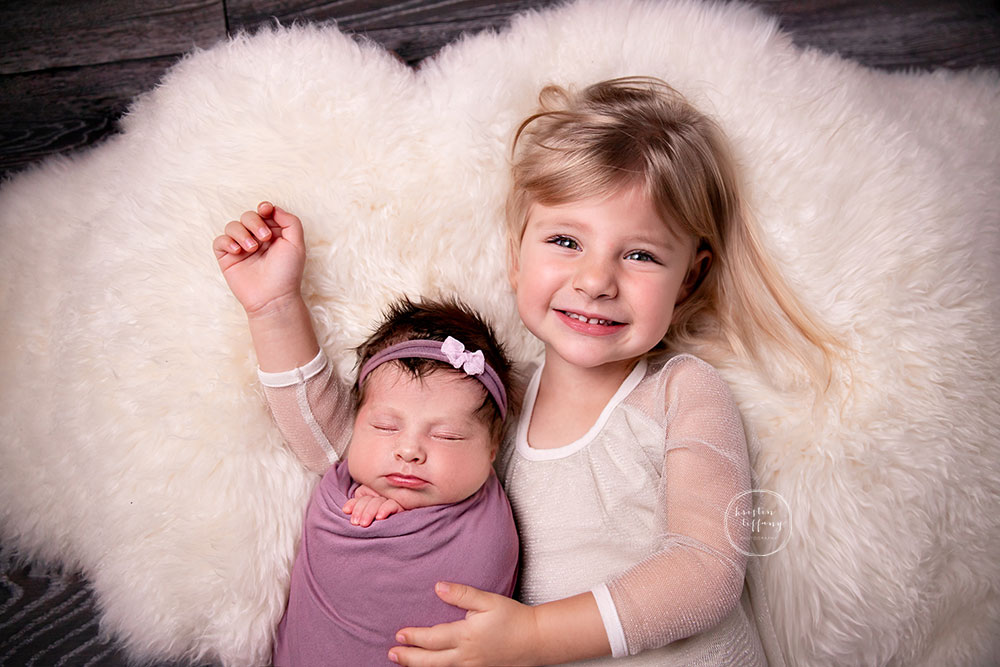 a photo of a newborn baby girl and her sister at her newborn photo session