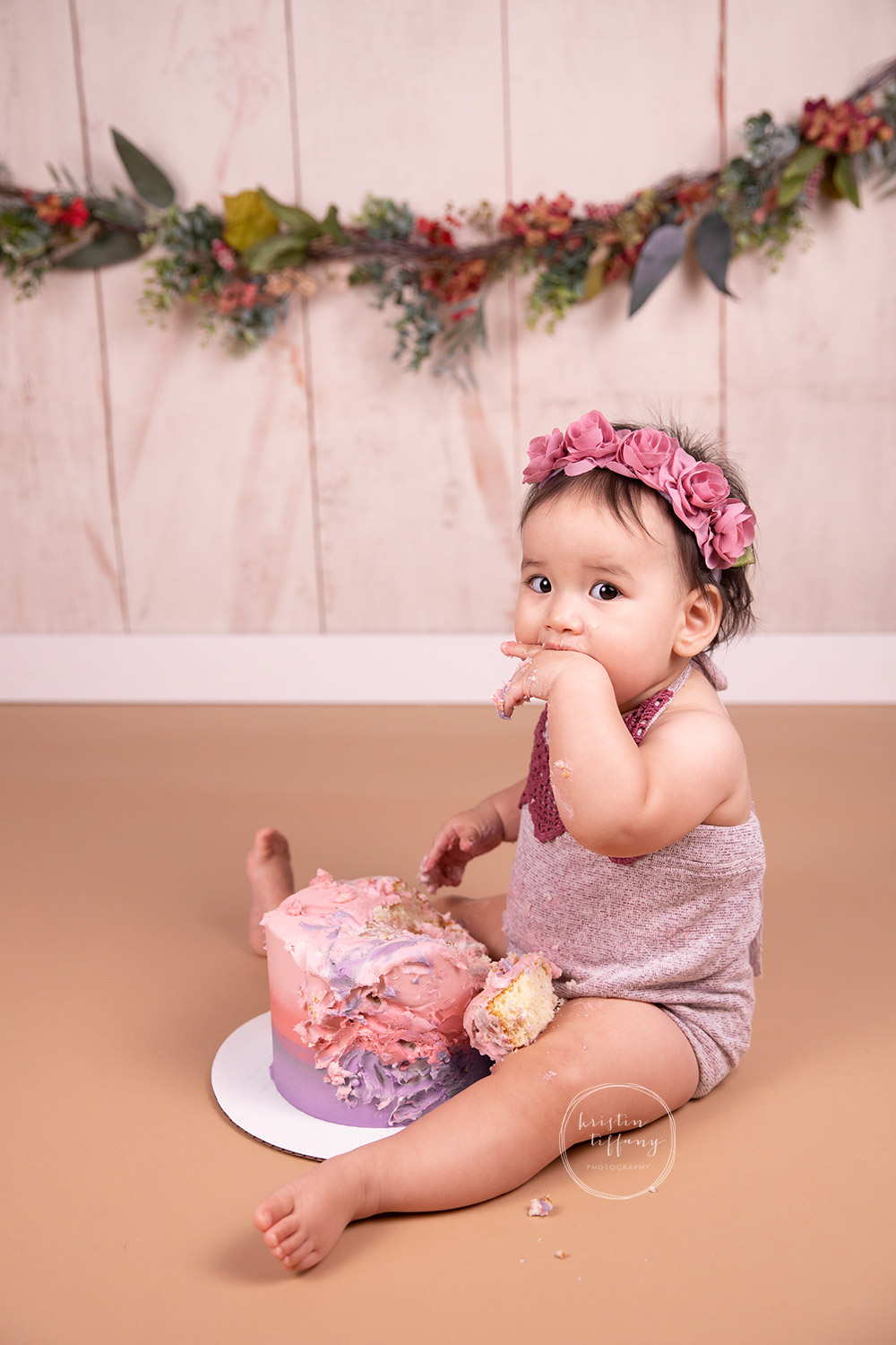 a photo of a baby girl at a cake smash photo session