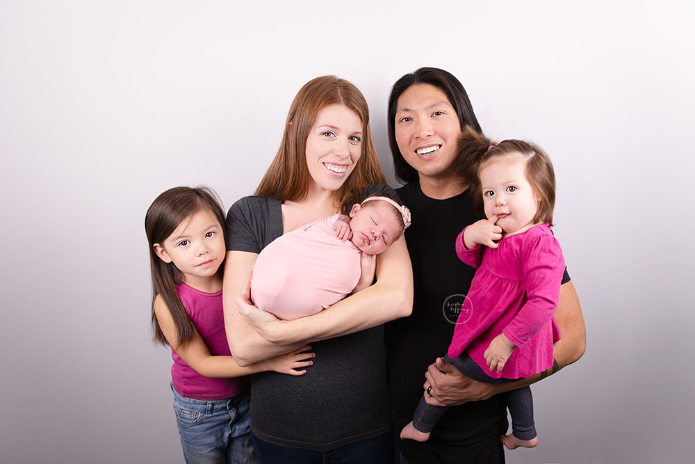 a photo of a baby girl and her family at her newborn photo session