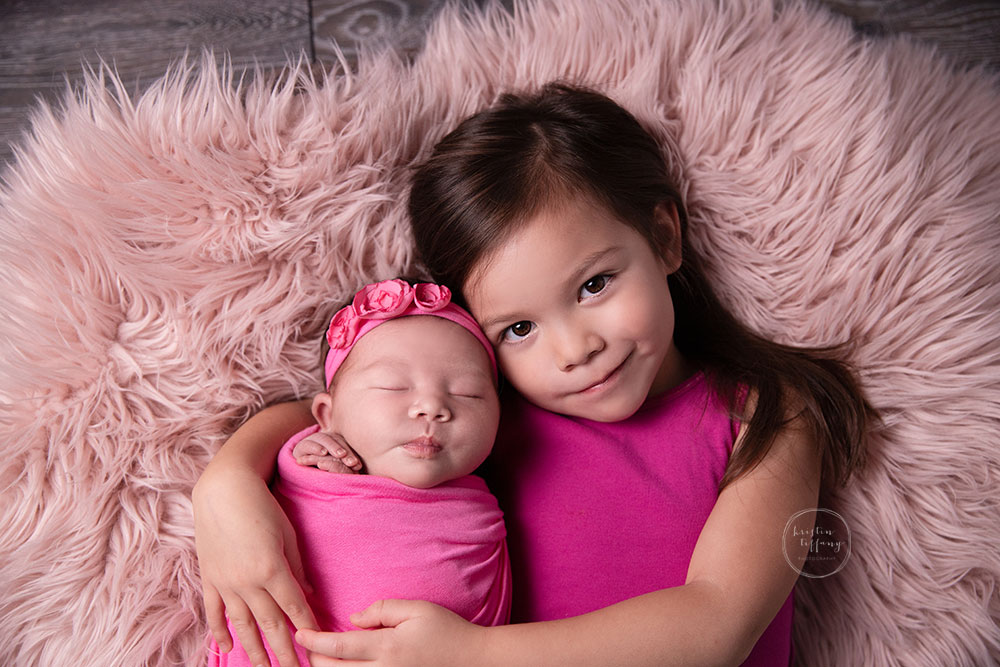 a photo of a baby girl and her big sister at her newborn photo session