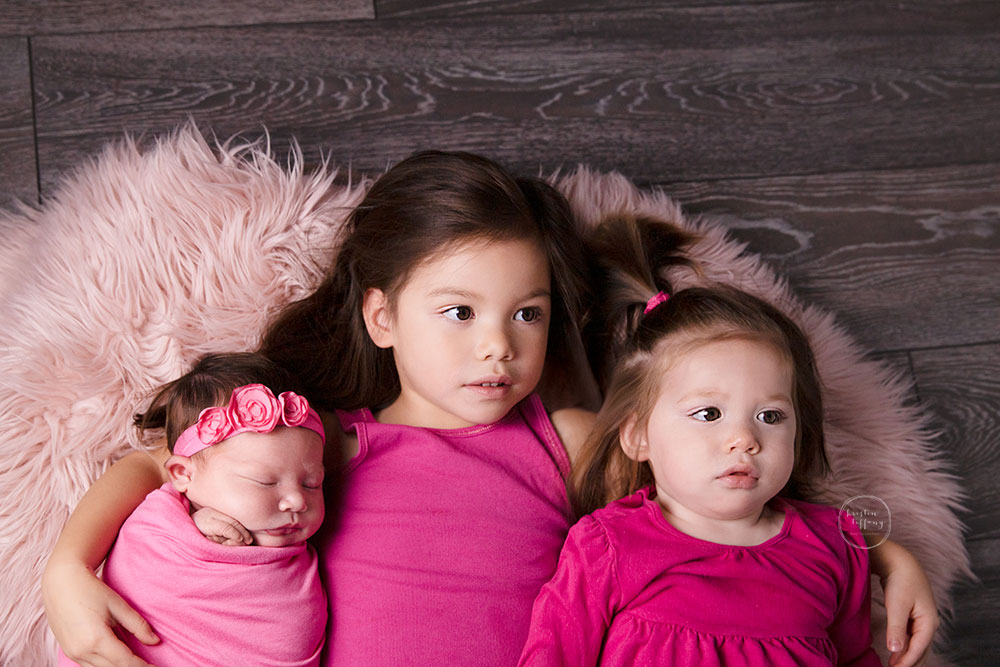 a photo of a baby girl and her sisters at her newborn photo session
