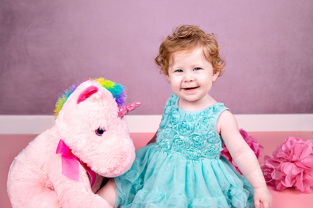 a photo of a baby girl at her unicorn cake smash photoshoot