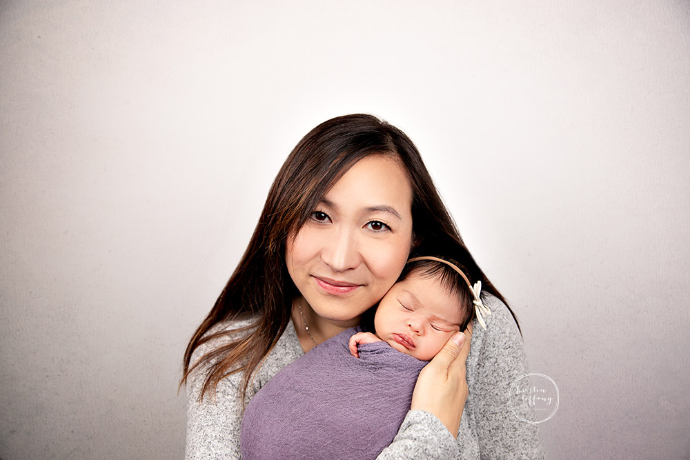 a photo of a baby girl and her mother at her newborn photo session