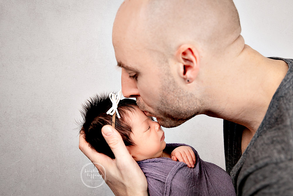 a photo of a baby girl and her father at her newborn photo session