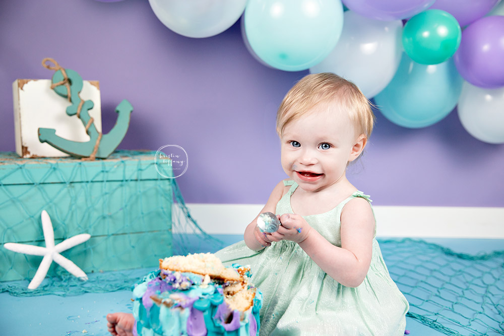 a photo of a baby girl at a cake smash session with Kristin Tiffany Photography